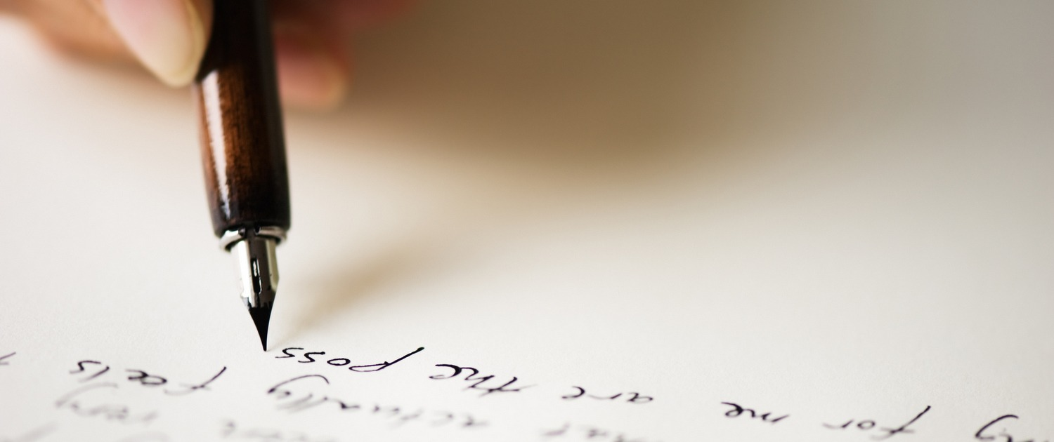close up of pen writing letter