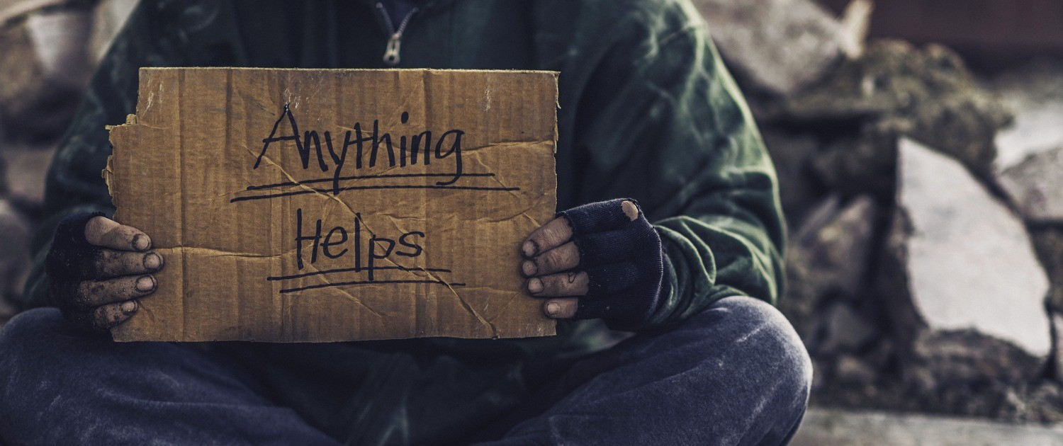 """Homeless person holding cardboard sign that says """"Anything Helps"""""""